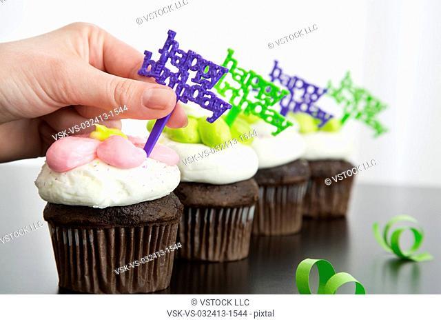 Hand decorating birthday cupcakes