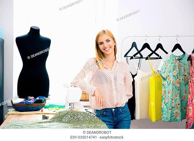 Happy young designer standing in workshop