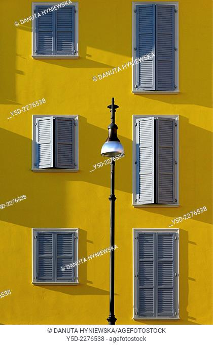 part of facade with windows and wooden shutters, street lamp in front, Formigine, province of Modena, Emilia-Romagna, Italy