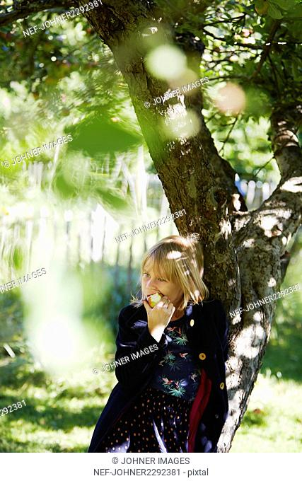 Blond girl eating apple in orchard