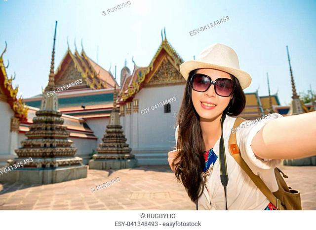 Asian japanese woman taking self portrait selfie photo with smartphone camera on asia travel. Happy candid tourist on wat pho temple building