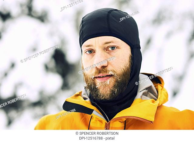 Portrait of a man with a frosty beard wearing a head covering against a snowy background; British Columbia, Canada