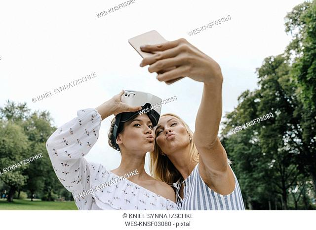 Two young women with VR glasses taking a selfie in a park