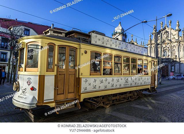 Vintage tram in Vitoria parish of Porto, Portugal. Carmelite Church (Igreja dos Carmelitas Descalcos), Carmo Church (Igreja do Carmo) on background