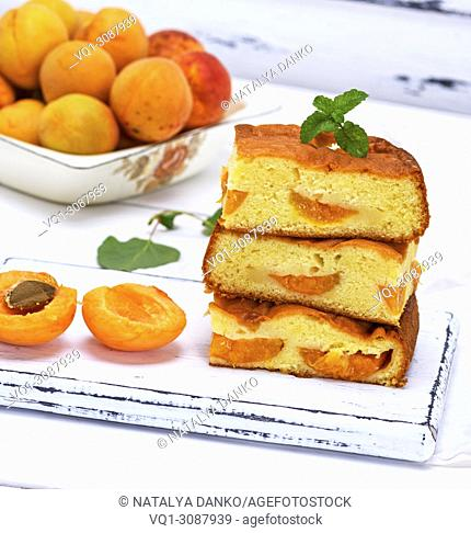 stack of biscuit pie with apricots on a white wooden table, sponge cake