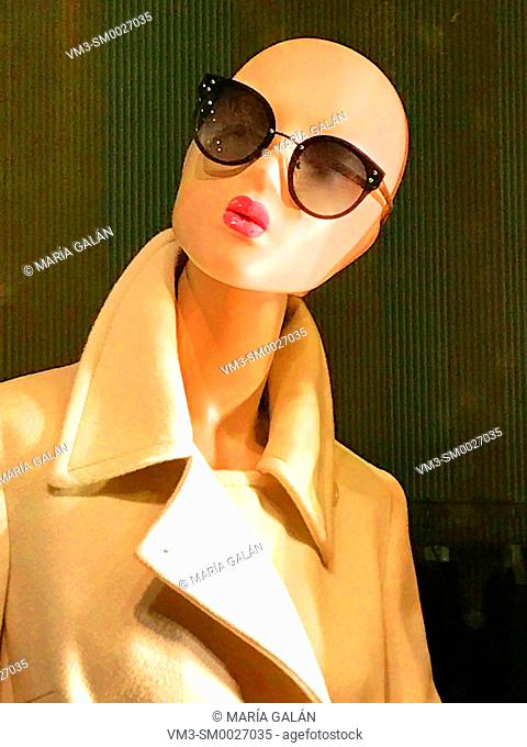Mannequin wearing coat and sunglasses