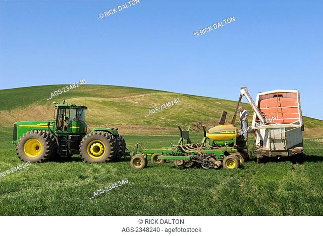 Agriculture - Loading an air seeder with wheat seeds to replant snow damaged areas of winter wheat in the rolling hills of the Palouse Region / near Pullman