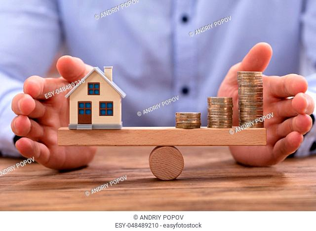 Small House Model And Stacked Golden Coins Balancing On Wooden Seesaw