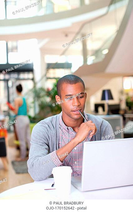 Portrait of confident businessman using laptop and writing on notepad in office