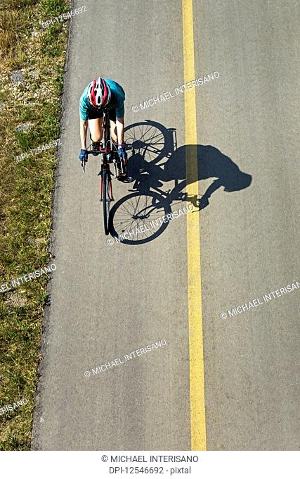 Aerial view looking down on a female cyclist on a paved pathway with shadow of cyclist; Calgary, Alberta, Canada