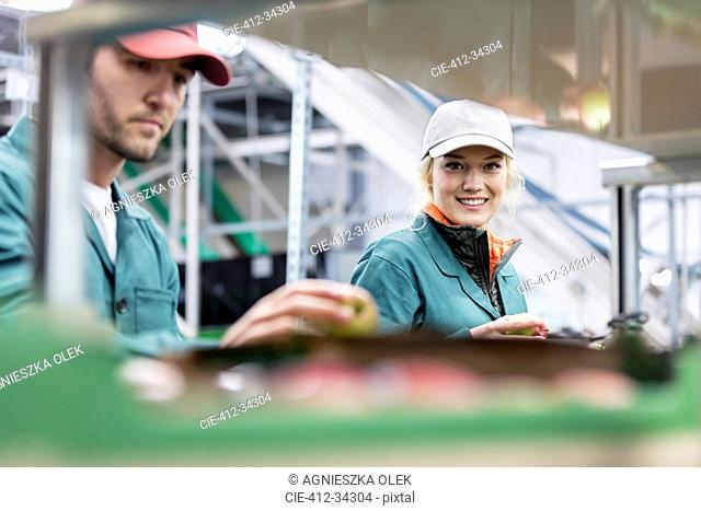 Portrait smiling female worker inspecting apples in food processing plant