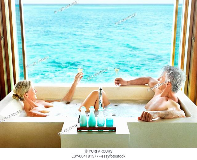 Portrait of happy couple in bathtub enjoying a glass of drink - Relaxing holidays