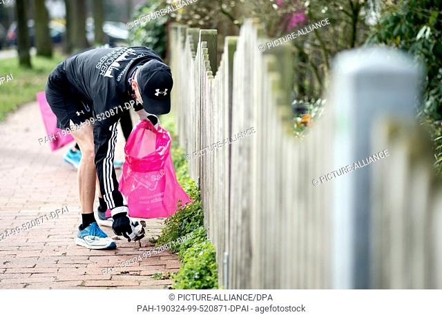 24 March 2019, Lower Saxony, Hannover: A jogger with gloves and a garbage bag collects garbage lying on the ground around the Noltemeyer Bridge in the Bothfeld...