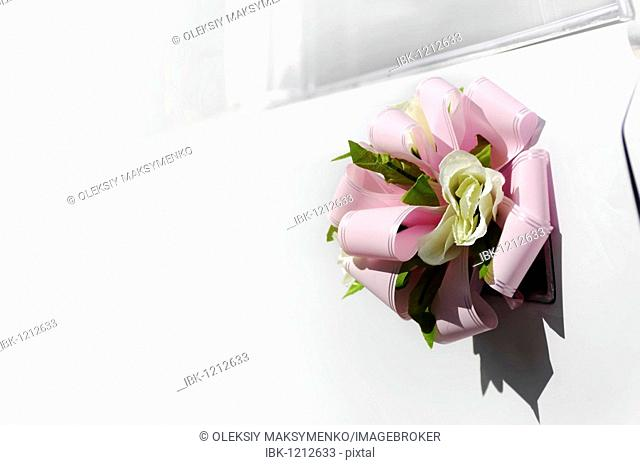 Flower with a pink bow on door handle of a white wedding limousine