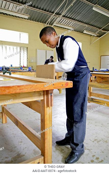 School boy clamping wood in woodwork classroom, St Mark's School, Mbabane, Hhohho, Kingdom of Swaziland