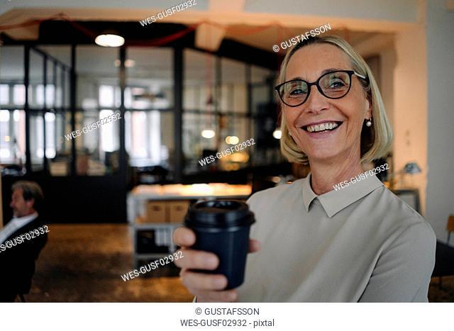 Portrait of happy mature businesswoman having a coffee break in office
