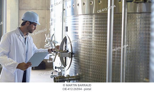Vintner in lab coat and hard hat examining stainless steel vat in cellar