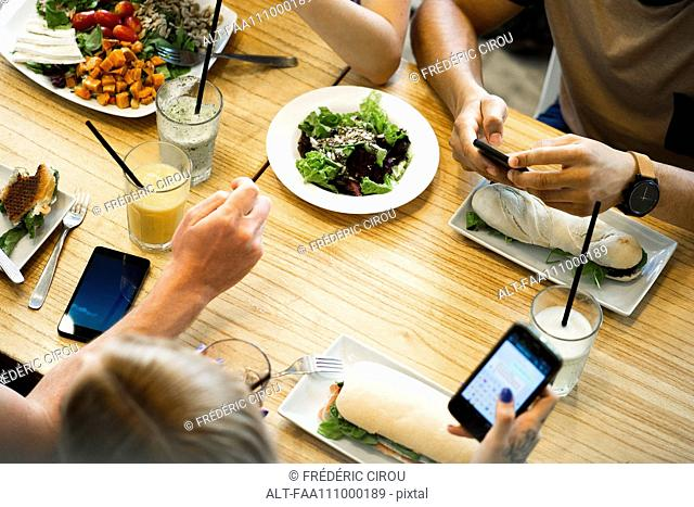 Friends using smartphones while eating in restaurant