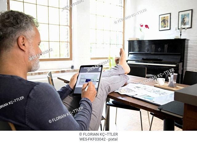 Mature man working from his home office with feet up, using tablet