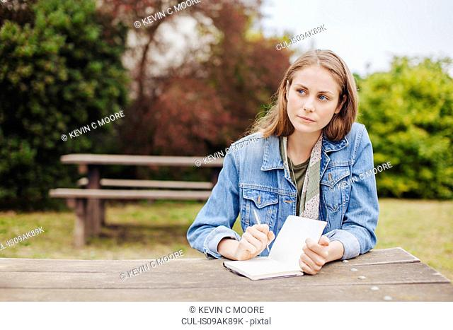 Young woman sitting at picnic bench in park writing in notebook