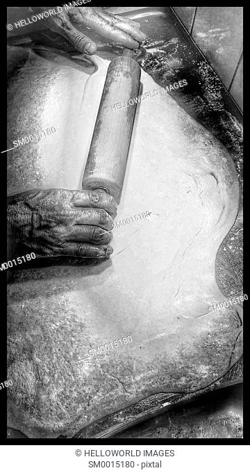 Male baker rolling out dough for pizza with wooden rolling pin on metal surface