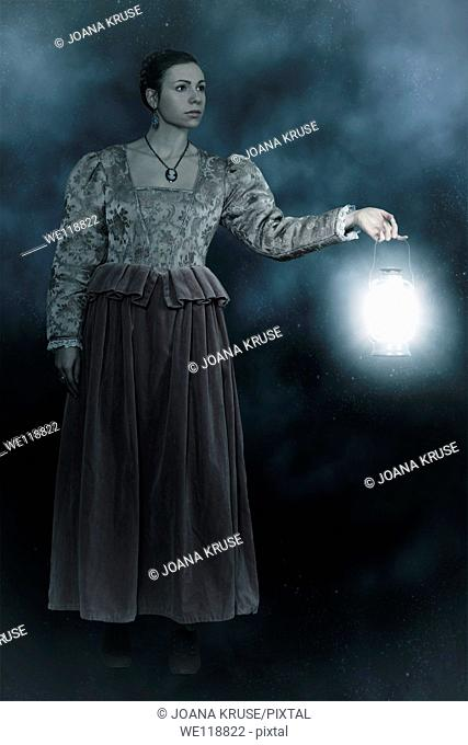 a woman in a victorian dress is holding a lantern in the dark