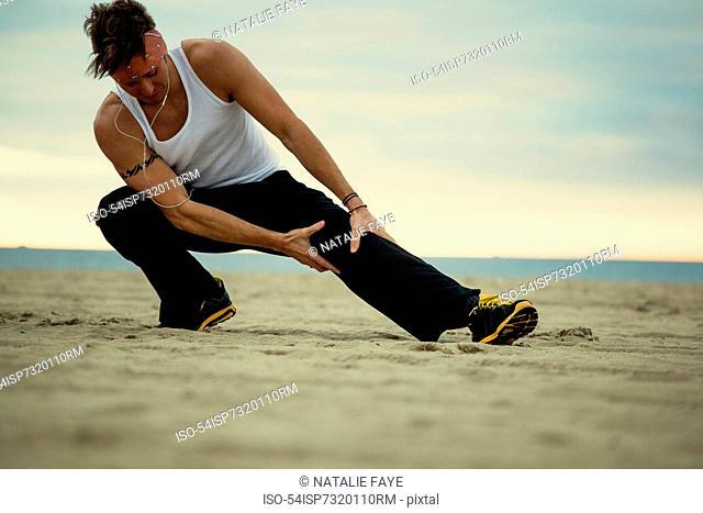 Man stretching on beach