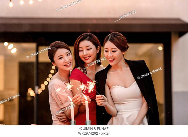 Three young smiling women lighting candles at party