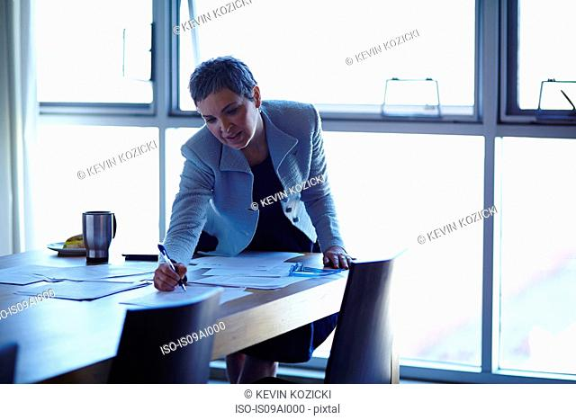 Mature businesswoman at conference table checking papers
