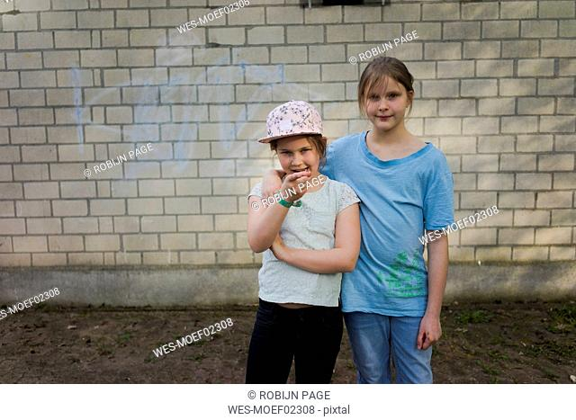 Portrait of two girls standing in front of a brick wall