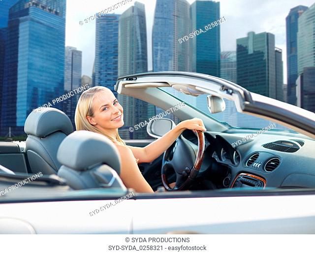 woman driving convertible car over singapore city