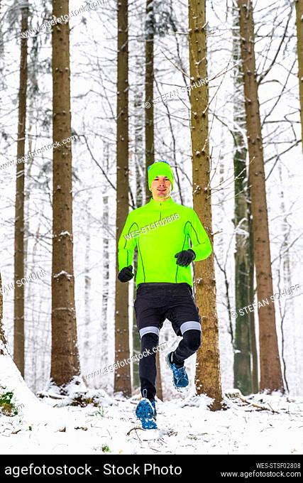 Male athlete running on snow in forest during winter