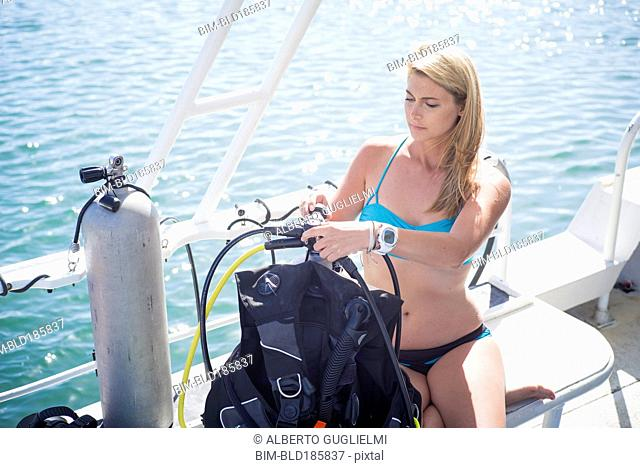 Caucasian diver checking equipment on boat