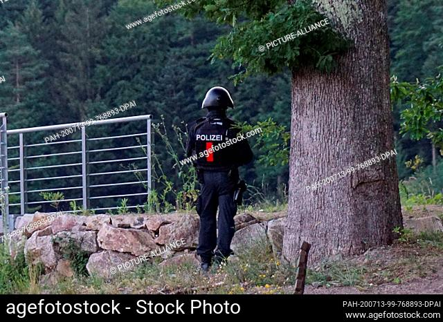 13 July 2020, Baden-Wuerttemberg, Oppenau: A policeman stands in front of a wooded area on a road near Oppenau. The day before