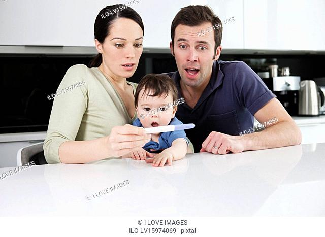 A couple and their baby son looking surprised at a pregnancy test result