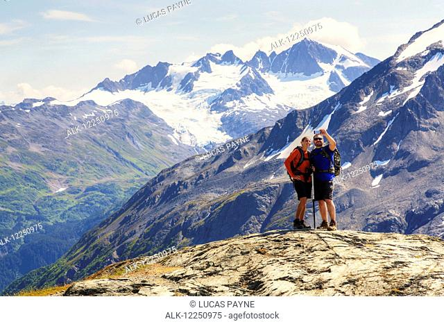 Hikers take a selfie with a smart phone from the Harding Icefield Trail near Seward, Kenai Fjords National Park, Kenai Peninsula, Southcentral Alaska, HDR