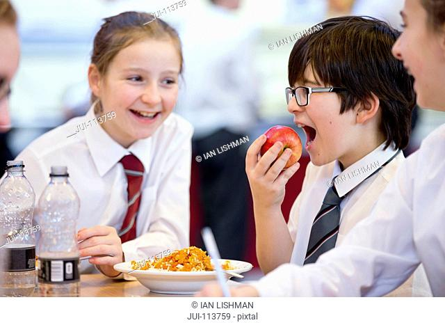 Smiling middle school students eating lunch and talking in school cafeteria