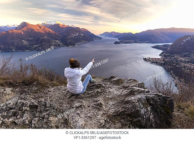A girl staring at the view of the center and the two branches of Lake Como during a windy winter sunset from Breglia. Plesio, Como Lake, Lombardy, Italy