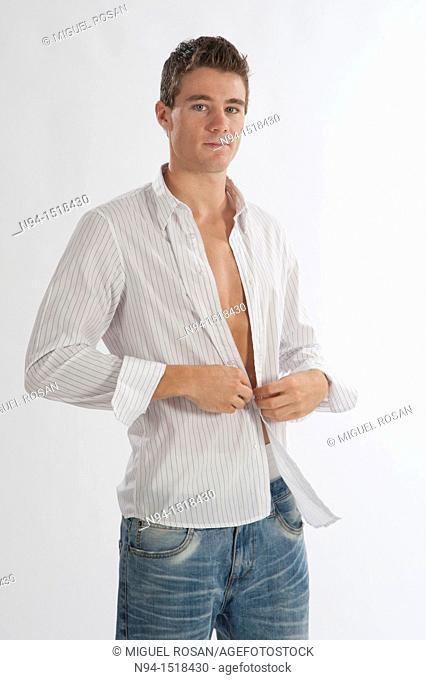 Half-length photograph of a teenage boy putting on his white shirt