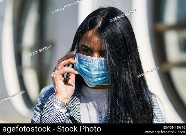 Girl with a mask to avoid contagion walking down the street. Coronavirus concept