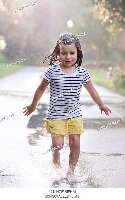 Barefoot girl running through puddles on rainy street