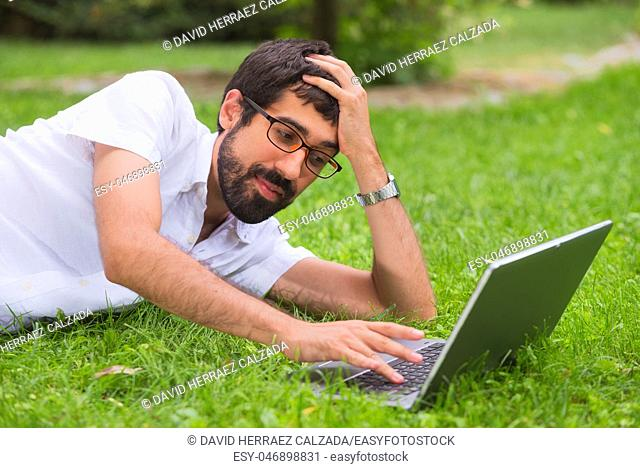 Young man working on his laptop while lying on the grass of the park. bored expression