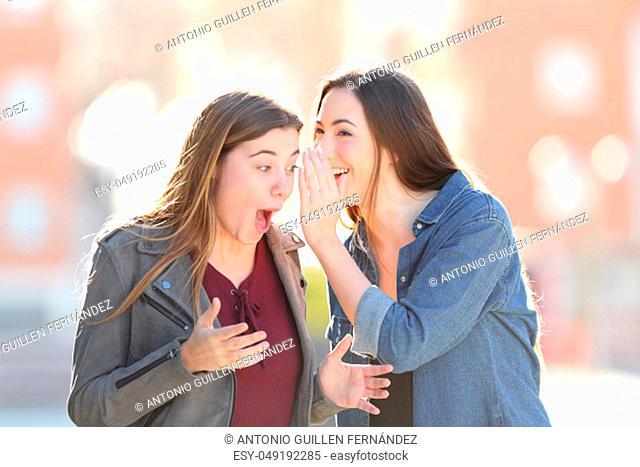Gossip woman telling secret to her surprised friend in the street