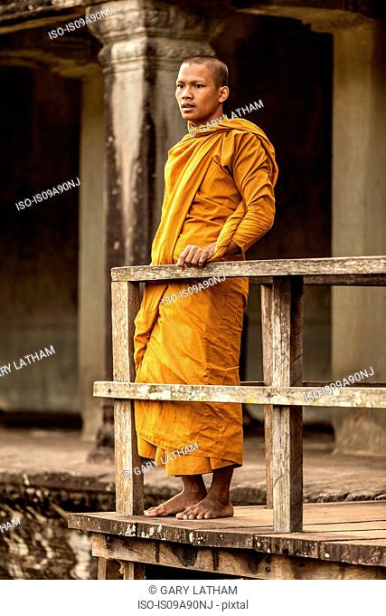 Young Buddhist monk standing by railing in temple, Angkor Wat, Siem Reap, Cambodia