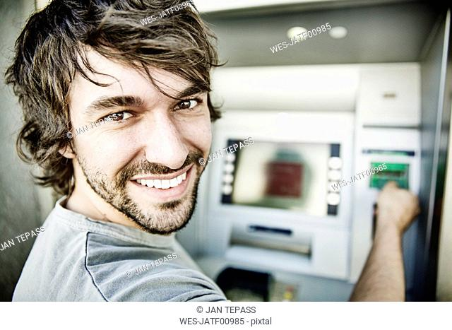 Portrait of laughing young man using cash machine