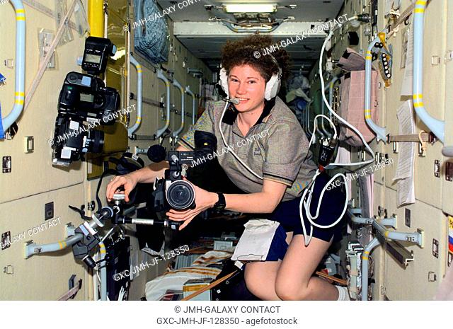Astronaut Susan J. Helms, Expedition Two flight engineer, mounts a video camera onto a bracket in the Zarya or Functional Cargo Block (FGB) of the International...