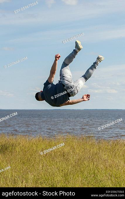 Athletic man performing flips on the hill over the river at sunny day, close up