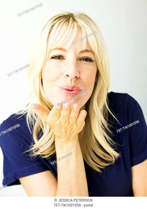 Studio portrait of blonde woman blowing kiss