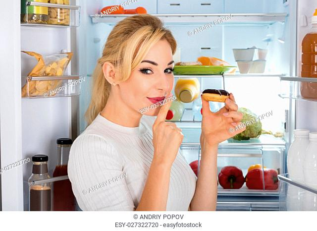 Young Woman Holding Donuts With Finger On Her Mouth In Front Of Her Refrigerator