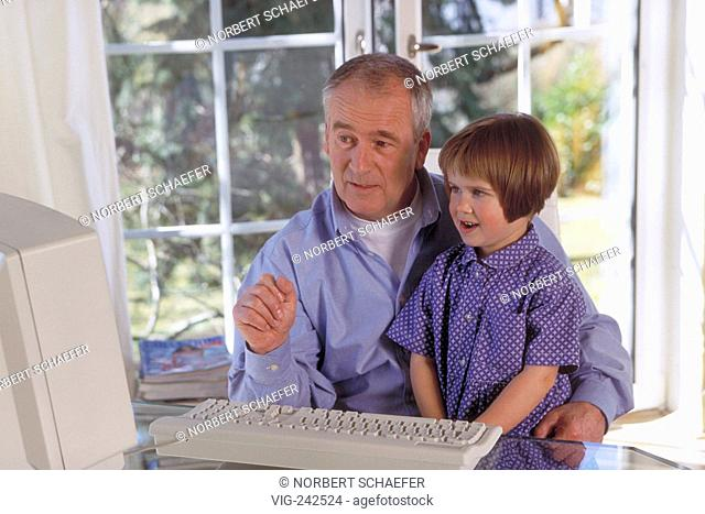 indoor, 4-year-old girl sits with her grandfather at the table near the window in front of a computer  - GERMANY, 26/02/2005